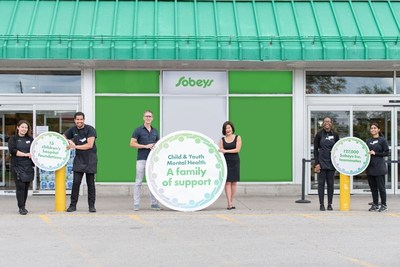 """Mark Hierlihy, President and CEO, Canada's Children's Hospital Foundations, Sandra Sanderson, Senior Vice President, Marketing, Sobeys Inc. (centred, left to right) and Sobeys Inc. teammates celebrate the launch of historic partnership, """"A Family of Support"""" Child and Youth Mental Health Initiative, at Sobeys Queensway in Toronto, ON. (CNW Group/Sobeys Inc.)"""